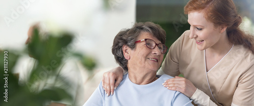 Close-up of a tender caregiver with her hands on the shoulders of a senior woman inside her home. Blurred surrounding. Panorama. - 211127930