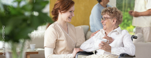 Young caretaker making a geriatric pensioner in a wheelchair laugh during leisure time in a common room of a luxury rehabilitation center. Blurred surrounding. Panorama.