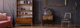 Gold chair standing in dark grey room interior with two vintage wooden cupboards with decor, books and fresh tulips - 211131174