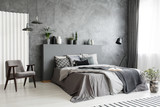 Modern grey bedroom interior with big bed with pillows and linen. Comfortable armchair next to the bed. Real photo. - 211131919