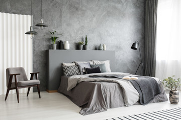 Modern grey bedroom interior with big bed with pillows and linen. Comfortable armchair next to the bed. Real photo. © Photographee.eu
