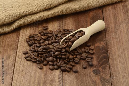 Fotobehang Koffiebonen Granos de café y cuchara de madera sobre fondo de madera
