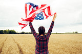 Young beautiful woman holding USA flag - 211144350