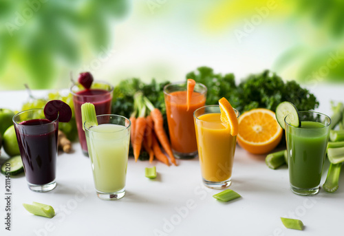 Wall mural healthy eating, drinks, diet and detox concept - glasses with different fruit or vegetable juices and food on table over green natural background