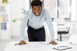 architecture, construction business and people concept - smiling african american architect with blueprint working at office