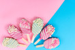 Different cake pops in form of popsicle on stick on pink and blue background.