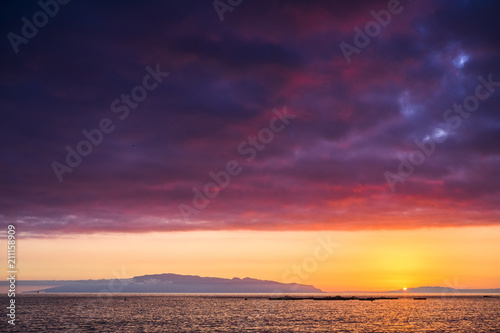Fotobehang Aubergine amazing scenic landscape taken during a wonerful sunset on the ocean. La Gomera oceanic island in background with clouds and water in red and orange colors. timeless moment with the sun going down
