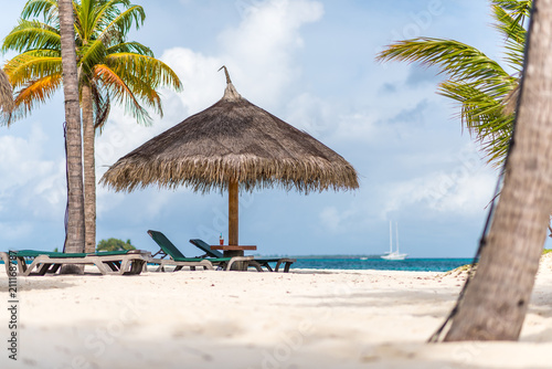 Strohschirm und Strandliegen und Getränk auf Tisch mit Palmen und Meer im Hintergrund