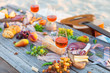 Leinwanddruck Bild - Picnic on beach at sunset in boho style. Romantic dinner, friends party, summertime, food and drink concept