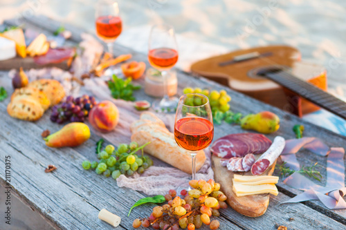Leinwanddruck Bild Picnic on beach at sunset in boho style. Romantic dinner, friends party, summertime, food and drink concept