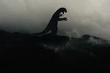 Silhouette eines Godzilla-artigen Monsters im Nebel auf einem Berg