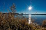 Sonnenstern über einem See - 211181763