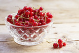 organic red currant berries from the garden in a glass bowl on rustic wood, close up with copy space - 211191749