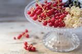 red and white currant berries in a glass bowl on rustic wood,close up shot with copy space - 211191995