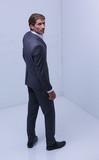 serious businessman standing in corner - 211207521