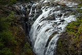 beautiful waterfall rushing into the gap of two giant rocks in the forest