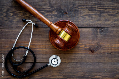 Fototapeta Medical law, health law concept. Gavel and stethoscope on dark wooden backgound top view copy space