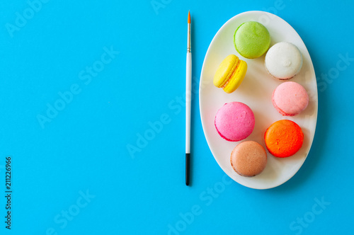 Fotobehang Macarons Colorful macarons cookies on a white plate, top view, food background concept.