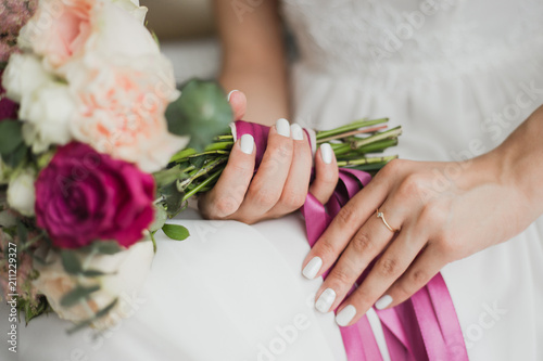 Leinwanddruck Bild Beautiful colorful wedding flowers in hands of young bride sitting alone in home interior. Fingernails with beautiful bridal manicure and engagement ring. Horizontal color photography.