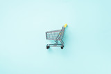 Fototapety Shopping cart on blue background. Minimalism style. Creative design. Top view with copy space. Shop trolley at supermarket. Sale, discount, shopaholism concept. Consumer society trend