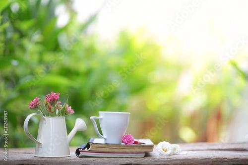 Różowy kwiat w biały puli i biały kubek z pamiętnika notatnik