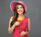 Woman in red dress wearing summer hat and holding yellow flower.
