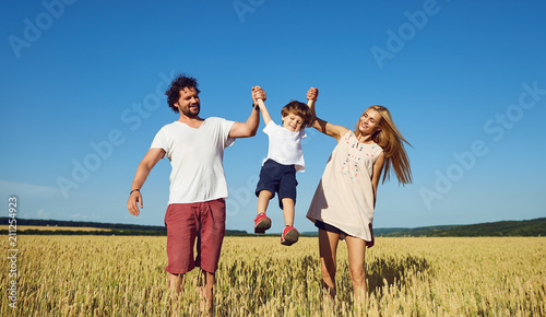 Happy family having fun playing in the field on a sunny summer day.