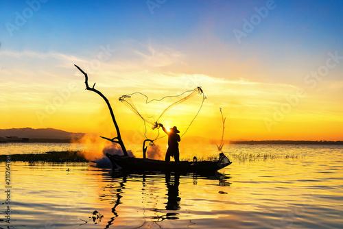 Leinwanddruck Bild Silhouette of asian fisherman on wooden boat ,fisherman in action throwing a net for catching freshwater fish in nature river