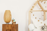 Two artificial cactuses and wicker lamp standing on wooden bedside table in white kid room interior - 211270122
