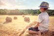 Leinwanddruck Bild - Boy sitting on a haystack in summer watching the sunset