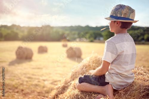 Leinwanddruck Bild Boy sitting on a haystack in summer watching the sunset