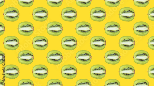 A seamless pattern with green kiwi on a yellow background - 211274511