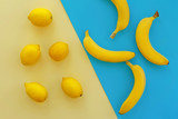 yellow bananas and lemons on bright blue paper, trendy flat lay. fruits modern image, top view. juicy summer vitamin abstract background. pop art style. creative minimalism.