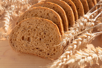 Bread with grain on wooden background.