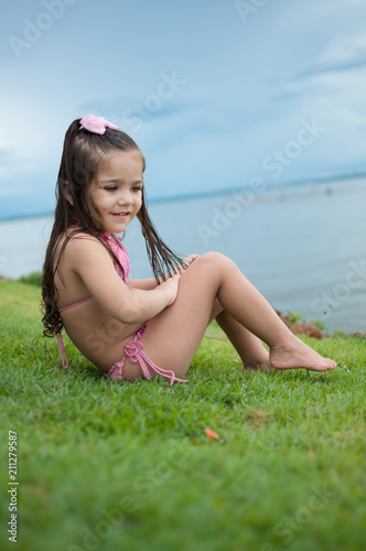 Foto Murales Beautiful girl playing in a park lawn and wonderful lake in the background with a wonderful blue sky