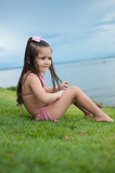 Beautiful girl playing in a park lawn and wonderful lake in the background with a wonderful blue sky