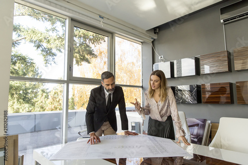 Foto Murales Young woman and senior businessman working together on project in modern office