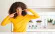 Leinwanddruck Bild - African american woman wearing yellow sweater at kitchen smiling confident showing and pointing with fingers teeth and mouth. Health concept.