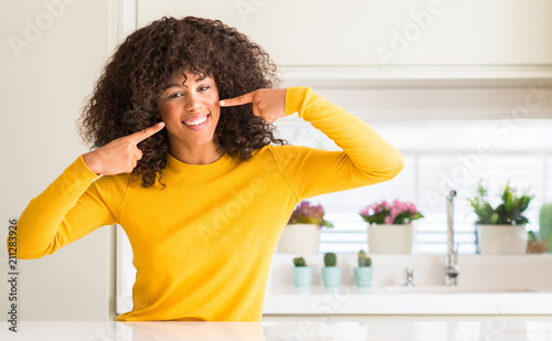 Leinwanddruck Bild African american woman wearing yellow sweater at kitchen smiling confident showing and pointing with fingers teeth and mouth. Health concept.