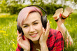 Young beautiful girl listening to music on headphones and lies on a green grass and dandelions.