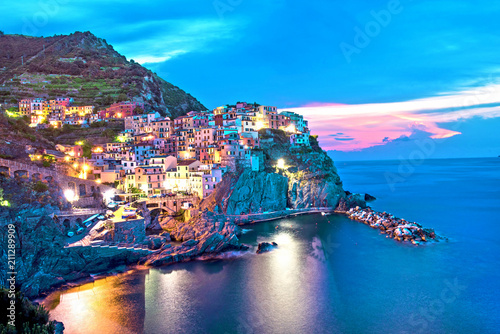 Fotobehang Liguria Magical beautiful landscape with bright colored houses on the rock on the sea coast of Manarola in Cinque Terre, Liguria, Italy, Europe in the evening