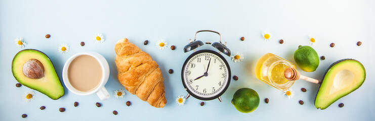 morning coffee in a white cup Croissant Avocado Awakening with an alarm clock Breakfast cheerfulness, a healthy breakfast freshness Banner Copy space © Natalya