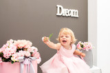 little girl blond playing flowers in a room decorated for a holiday in pink tones