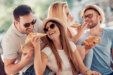Happy group of people eating pizza outdoors - 211304345