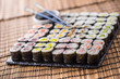 Collection of Sushi maki on slate board with soy sauce and chopsticks