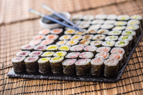 Fotobehang Sushi bar Collection of Sushi maki on slate board with soy sauce and chopsticks