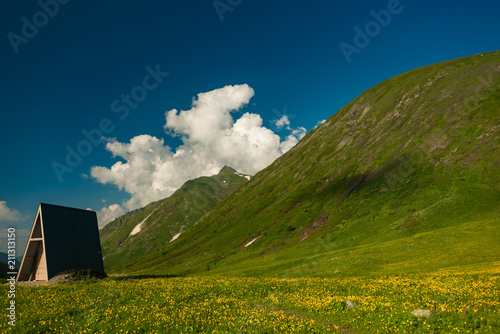 Fotobehang Nachtblauw Green slope of the high big mountain. Alpine meadows in the Caucasus Mountains. Flowers of all colors and grasses. Beautiful blue sky and clouds. Impressions from mountain tourism.