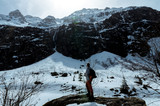 A lone traveler wandering in front of snowy peaks of mountains - 211315562