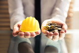Human Hand Holding Hardhat And Many Golden Coins