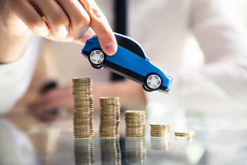 Person Flying Car Over Declining Stacked Coins © Andrey Popov